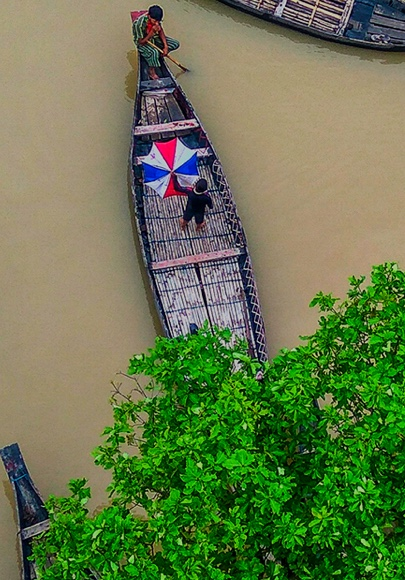 Overhead view of two locals rowing their handmade boat across a murky river