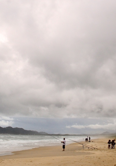 Some locals fishing on a sandy beach with an overcast sky